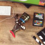 Desktop shot of a modern digital Cinema Camera and clapboard on stylish wooden desktop workplace / Background